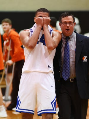 Zanesville senior Aronde Myers is consoled by assistant coach Nate Seekatz following the Blue Devils' 56-44 loss to Meadowbrook in a Division II district final on Saturday at Muskingum University.