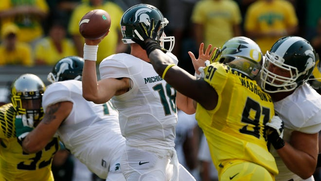 Michigan State quarterback Connor Cook, left, passes down field under pressure from Oregon's Tony Washington during the first quarter Saturday.
