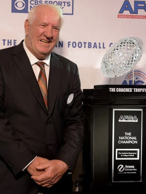 Former Clemson coach Danny Ford poses with the Amway Coaches Trophy at the 2017 American Football Coaches Awards in January.