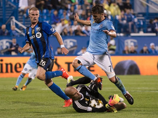 Montreal Impact goalkeeper Evan Bush cradles the ball away from New York City FC forward David Villa as Impact defender Kyle Fisher looks on during the second half of an MLS soccer match Wednesday, Sept. 27, 2017, in Montreal. (Paul Chiasson/The Canadian Press via AP)