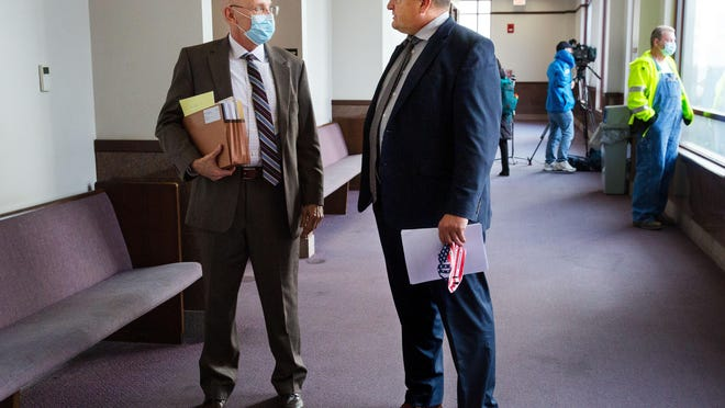 Attorneys John Kerley, left, and Thomas DeVore confer in the hallway outside a courtroom in the Sangamon County Building after a judge granted a temporary injunction sought by Sangamon County over four restaurants in Springfield that were continuing to operate without food permits. The restaurants were serving indoor diners Sunday in defiance of the mitigations that went into effect last week and their licenses were suspended. The attorneys represent the restaurants involved.