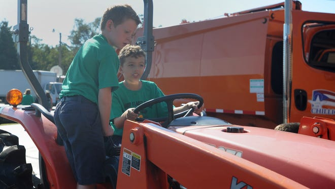 Sam Byrd, left, and Dane Liggins climb into the driver's seat of a piece of farm equipment Thursday at Bishop Flaget School. The students gathered around farm equipment, utility vehicles, a sheriff's cruiser and more as part of a school-wide STEM project.