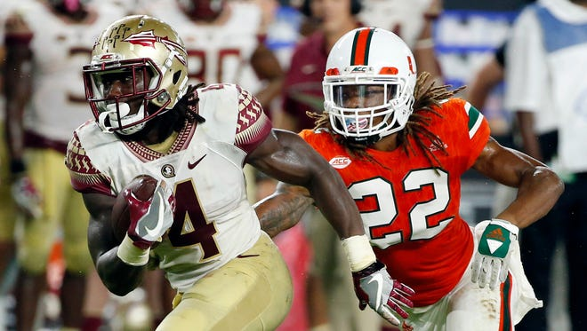 Florida State running back Dalvin Cook carries the ball ahead of Miami defensive back Sheldrick Redwine during the second half Oct. 8, 2016 in Miami Gardens, Fla.