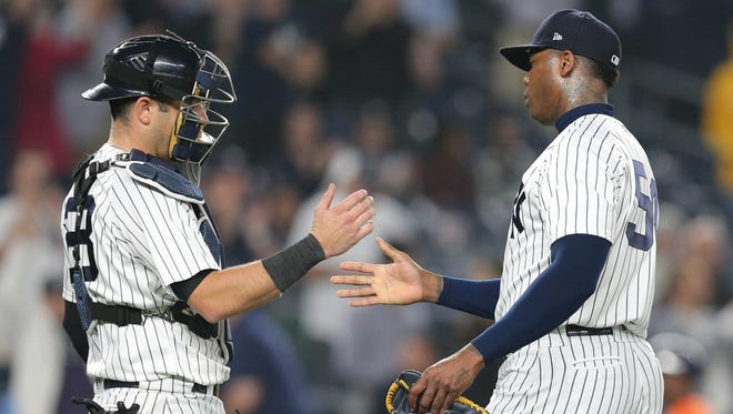 New York Yankees relief pitcher Aroldis Chapman and New York Yankees catcher Austin Romine shake hands after defeating the Houston Astros at Yankee Stadium.