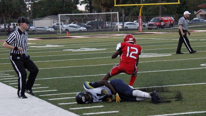Referees from the Greater Naples Football Officials Association look on as Immokalee running back Jhaman Mythril breaks a tackle against Lehigh Senior in the team's spring classic game at Gary Bates Stadium in Immokalee on Thursday, May 26, 2016.