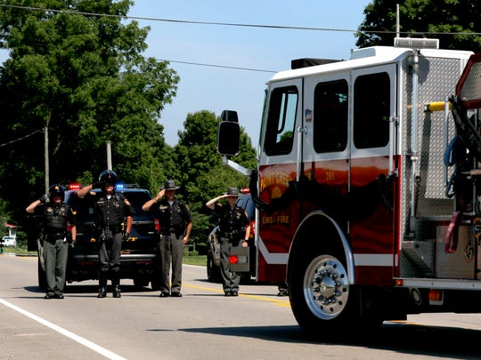 Ross County Sheriff's Deputies salute as Paint Creek fire engine carrying the body of firefighter Joseph Patterson turns into Londonderry Cemetery Friday afternoon, June 29, 2018.