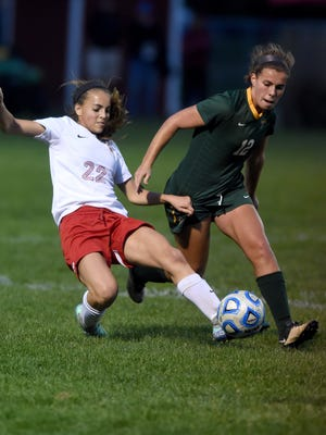 Richmond's Payton VanMiddlesworth slide tackles against Floyd Central's Katie Yankey Wednesday, Oct. 12, 2016 in the girls soccer regional game at East Central High School.