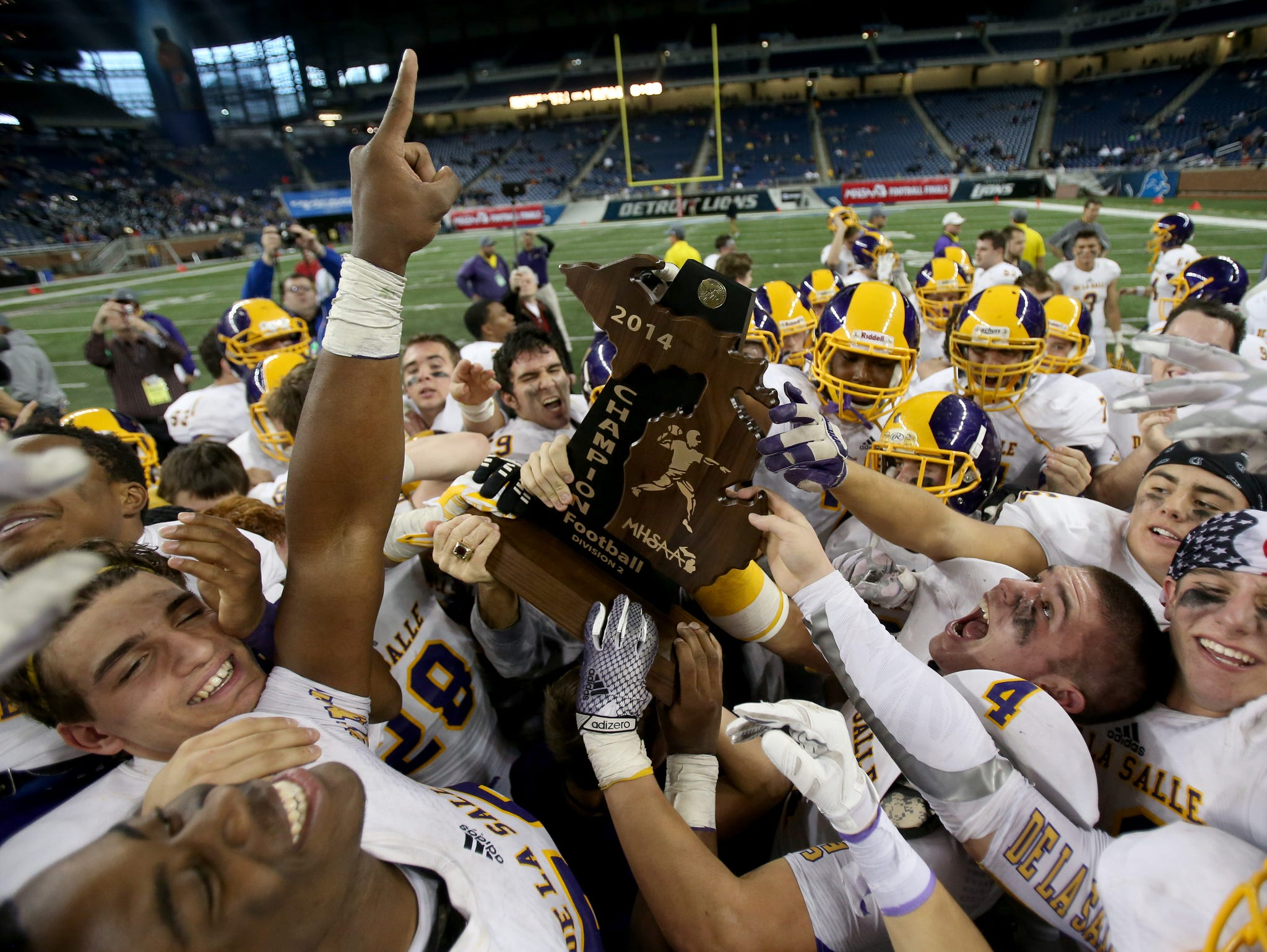 Warren De La Salle celebrates its 44-8 win over Muskegon Mona Shores high school in the Division 2 state title game on Nov. 28, 2014, at Ford Field.