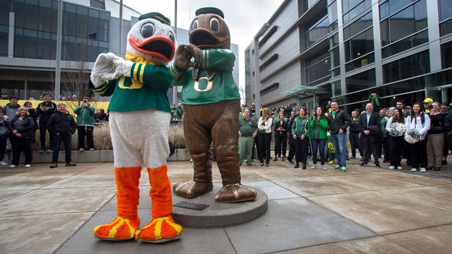 Oregon mascot Puddles the Duck imitates the pose of the newly unveiled bronze Duck statue in front of Matthew Knight Arena in 2016. (Brian Davies/The Register-Guard)