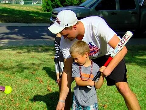 NubAbility founder Sam Kuhnert works with a young boy to teach him baseball. Kuhnert, who was born without his left hand, played two seasons of college baseball as a right-handed pitcher.