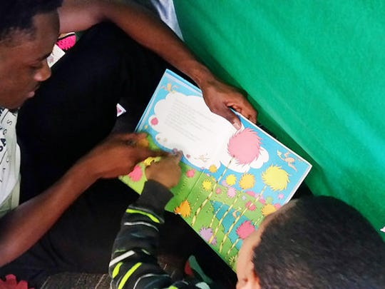 """A young student reads """"The Lorax"""" with his Mount Saint"""