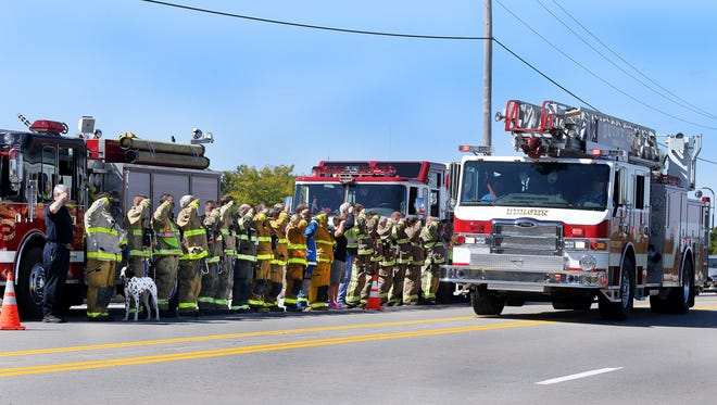 First responders from surrounding companies stand at attention on Route 33A over Interstate 490, as a procession carrying the body of a colleague, a volunteer firefighter and EMT, who was killed in a motor vehicle accident earlier in the morning while on a call.
