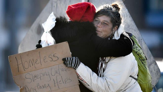 Jerrilyn Collier is hugged by Kathryn Davenport after she receives a gift basket along Spring Street in Nashville, Tenn., Friday, Dec. 15, 2017.