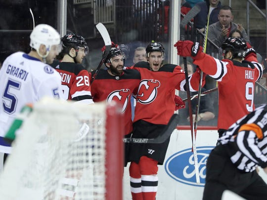 New Jersey Devils players celebrate a goal by right wing Kyle Palmieri, center, as Tampa Bay Lightning defenseman Dan Girardi (5) skates by during the second period of an NHL hockey game, Saturday, March 24, 2018, in Newark, N.J.