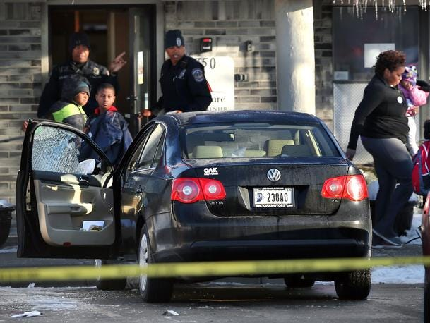 Children and adults leave KinderCare Learning Center on Feb. 18, 2014. The black Volkswagen driven by Shirley Justice, who was critically injured, remained at the scene in the late morning, its driver's door window shattered by bullets.