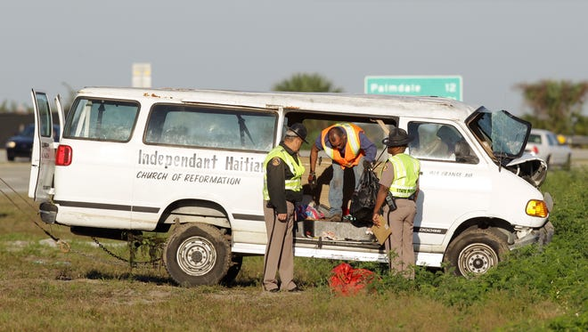 A worker, center, removes purses from a van after it was removed from a canal at the intersection of US 27 and State Road 78 West, Monday, March 30, 2015, near Moore Have, Fla. Eight people were killed and 10 injured when the church van ran through a stop sign, crossed all four lanes of a rural highway and crashed into in a canal.  (AP Photo/Luis M. Alvarez)