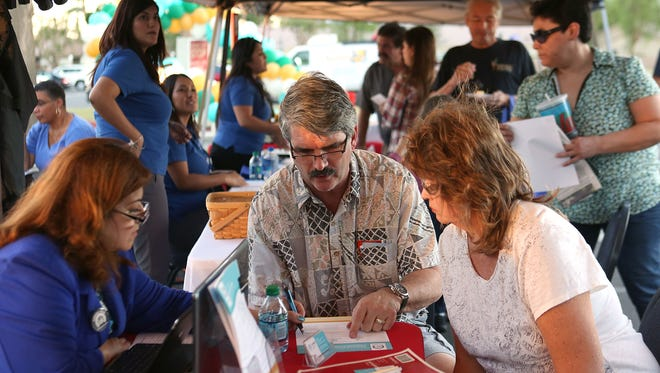 Brandon, center, and Dawn LeValley, right, receive information about the Covered California health insurance exchange during a promotional stop by the Covered California bus tour at JFK Hospital in Indio, Monday, November 2, 2015.