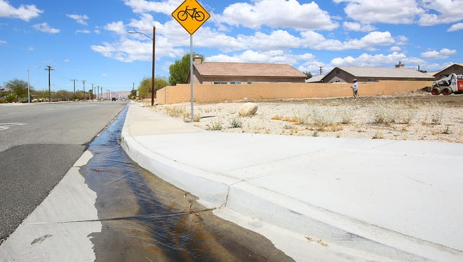 Water flows down a gutter along Two Bunch Palms Trail in Desert Hot Springs on May 18, 2016.