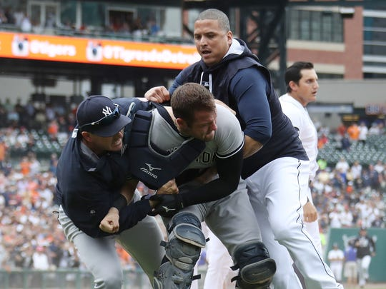 Victor Martinez tries to restrain Austin Romine during the Tigers-Yankees brawl at Comerica Park in August.