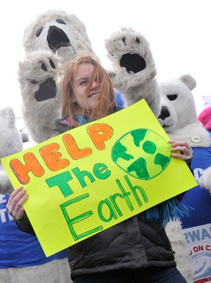 Climate Change rally participants dressed as polar bears pose for a photo with Zoe Jenkins, a George Washington University student on the National Mall during rally before a march from the National Mall from the Washington Monument to the White House in Washington, DC.