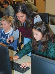 Celina Juarez helps Tarn Reilley of Santa Catalina School with computer coding during a Nov. 18 workshop at Hartnell College. Juarez is member of herScript, a group that supports gender equality in technology and does community outreach.