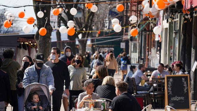 Pedestrians enjoy the sunny weather in the Brooklyn borough of New York City.