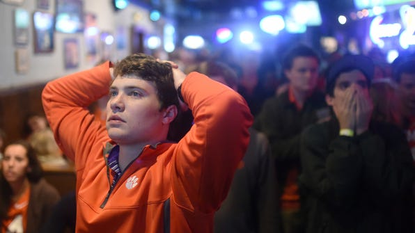 FILE - In a Jan. 11, 2016 file photo, Clemson fan Trey Funderburke reacts to an Alabama touchdown in the NCAA college football playoff championship game at Tiger Town Tavern, in Clemson, S.C. A year ago, Alabama beat Clemson 45-40 in a thriller. This is the first time in the college football title-game era that same two teams got to the season's final matchup. Alabama and Clemson play in Tampa, Fla. on Monday night. (AP Photo/Rainier Ehrhardt, File)