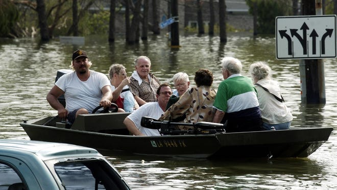 In this file photo, people are rescued from the Regions Bank on Robert E. Lee Boulevard on Aug. 30, 2005, in New Orleans. Storms have kept homeowner's insurance high in Louisiana, a study suggests.
