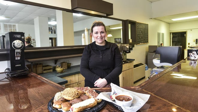 Emma Lister poses for a portrait behind the counter of her restaurant 8 Sisters Bakery in its new location in the Harding Center on Center Street. With her are a platter of her pastries and a bowl of chili which she now serves along with other items in the shop.
