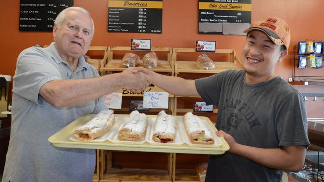 Longtime South Lyon Bakery owner Bill Stevanovic, left, shakes hands with its new owner Winson Chauv on May 19 in the Lafayette Street bakery. Chauv will soon take over the city mainstay after Stevanovic had operated it for more than 37 years. Stevanovic is training the new owner.