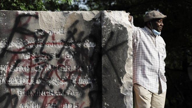 Robert Walker poses for a photograph on the remains of a Confederate memorial that was removed overnight in Birmingham, Ala., on Tuesday, June 2, 2020. The city took down the more than 50-foot-tall obelisk following protests over the police death of George Floyd and a night of vandalism in the city.