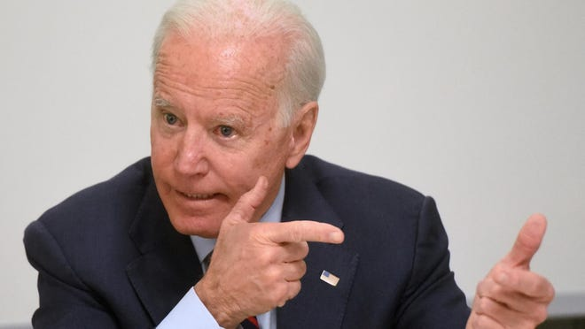 Joe Biden uses a gesture of holding a gun as he talks about Ukraine people getting killed right now as he speaks to the Seacoast Media Group Editorial Board on Monday morning.\r