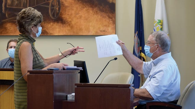 John Matthews, right, hands a signed document to County Clerk Janet Klasinski on Friday at the Leavenworth County Courthouse. Matthews served on the Board of County Canvassers in place of County Commissioner Mike Stieben.