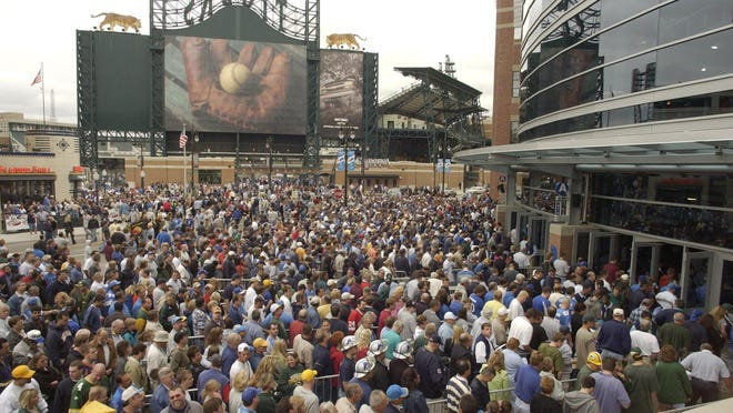 Fans file into Ford Field Sunday, Sept. 22, 2002, for the first regular season game of the Detroit Lions against the Green Bay Packers. Across the street, fans exit Comerica Park.