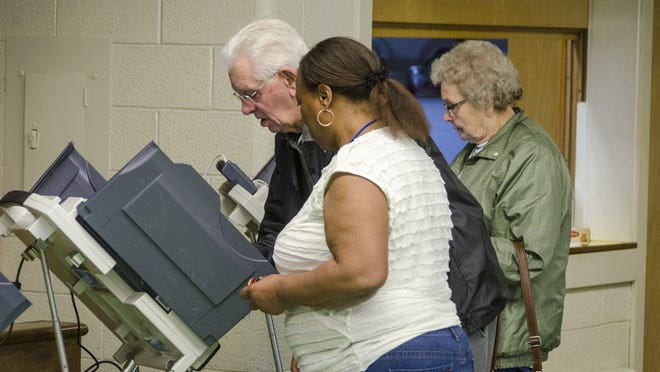 Poll worker Bernice Holder assists Edward and Irene Cervinski at the Mansfield 5A precinct during the 2015 election.
