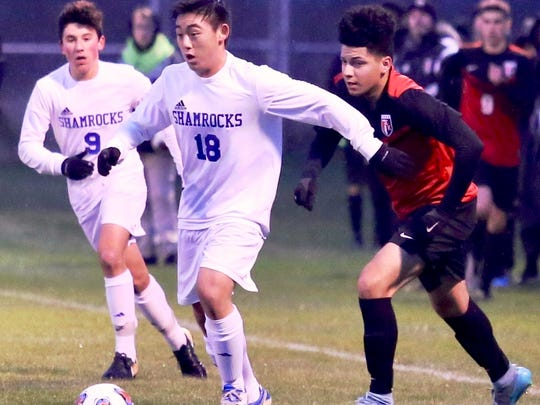 Catholic Central's Matthew Park (18) pushes the ball