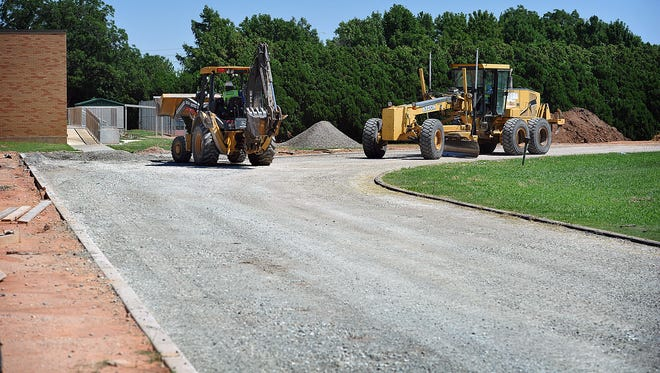 Workman with hellas Construction Inc. use heavy equipment to prepare the base material for resurfacing the running track at Barwise Middle School.