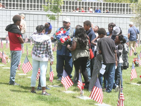With his family around him, Ambrose Shepherd prepares to place a wreath on the grave of his grandfather, Curtis Thorns, after the Memorial Day Ceremony Monday morning at the Northern Nevada Veterans Memorial Cemetery in Fernley.