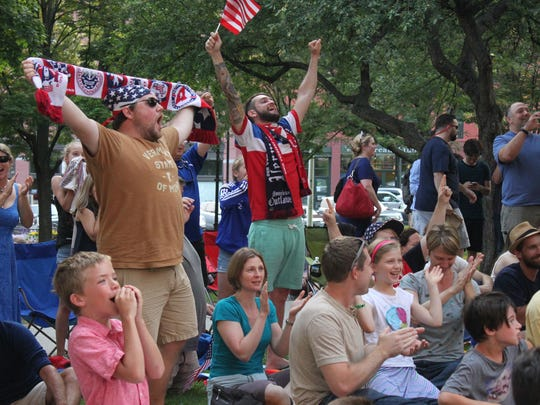 Scott Ranney, left, and Ian Bailey, right, stand and cheer in Burlington's City Hall Park after the U.S. women's soccer team scored a goal in the Women's World Cup final on Sunday.
