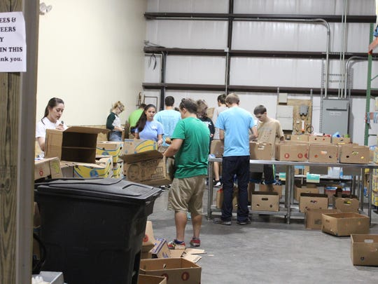 UWF Honor Society members volunteer Saturday at the Bay Area Food Bank in Milton by sorting and arranging food, and filling plastic bags with food for children facing hunger issues.