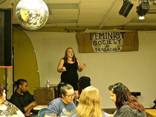 Ashley Faulkner welcomes attendees and guest speakers to the Pensacola Feminist Society's August meeting downtown at Sluggo's Vegetarian Restaurant.