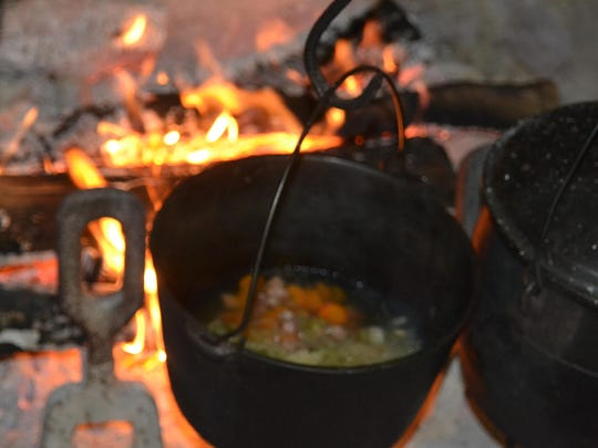 Tomato soup and cabbage jambalaya cook in kettles over an open hearth at Kent House. Sharing a meal with family was central to early Christmas celebrations, as it is today.
