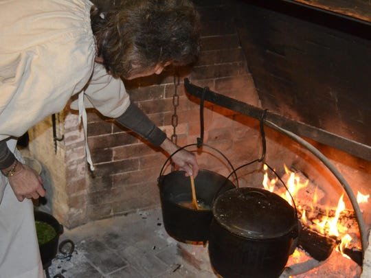 Volunteer Flora Luquette stirs a kettle of tomato soup at Kent House. Sharing a meal with family was central to early Christmas celebrations, as it is today.
