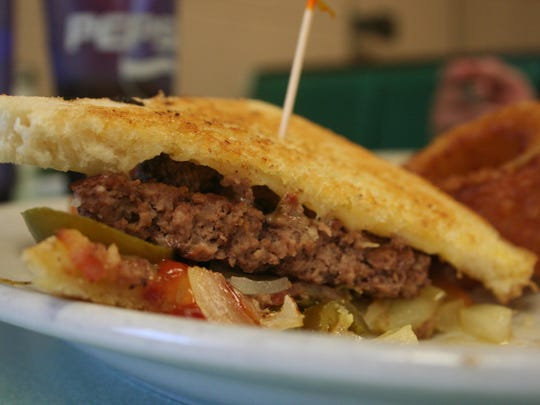 The Arlene's Burger is two ground beef patties, grilled onions, bacon, jalapeno peppers, pepper-jack cheese on toasted sourdough bread.