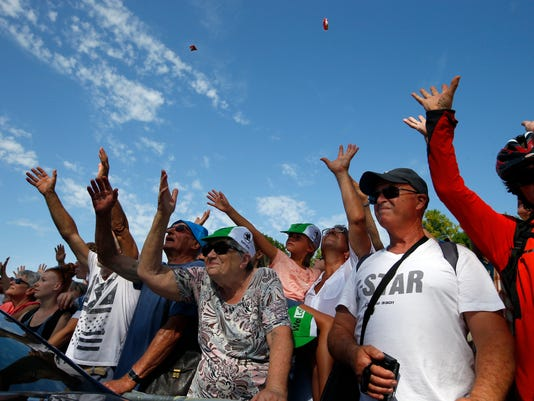 Spectators watch the publicity caravan pass prior to the start of the eighth stage of the Tour de France cycling race over 187.5 kilometers (116.5 miles) with start in Dole and finish in Station des Rousses, France, Saturday, July 8, 2017. (AP Photo/Peter Dejong)