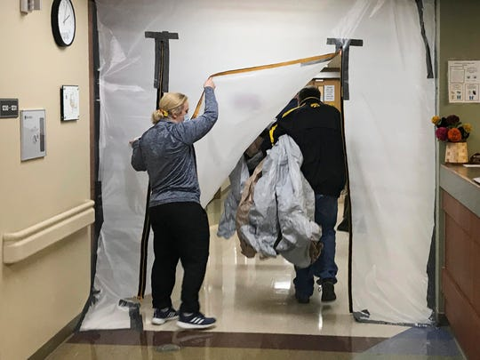 Occupational therapist Jennifer McMinn holds up a sheet of plastic as maintenance workers at Scotland County Hospital in Memphis, Mo., turn a regular ward into a COVID-19 ward in September. The small hospital is so full that it is sending patients to other hospitals up to two hours away.