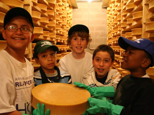 Fifth graders from De La Salle School in Freeport, Long Island show off a wheel of the Spring Brook Farm Tarentaise cheese, which they helped to turn and wash as part of their weeklong Farms for City Kids program visit to the Reading farm in 2010. The farm's cheese won this year's Best in Show honor at the 2014 American Cheese Society competition.