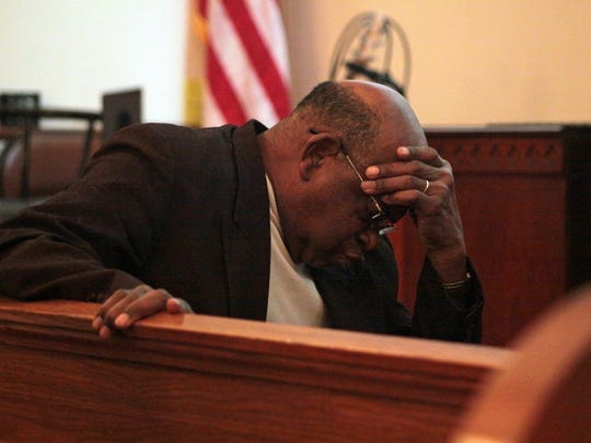 Pastor Willie Freeman bows his head as he listens to the message of several of his fellow clergy at a prayer vigil on Wednesday. Freeman is heading up the newly formed Coalition of Concerned Citizens.