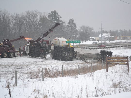 A tow truck operator prepares to pull an overturned tanker truck from along southbound Highway 41 in Oconto County, just south of County Highway I, about  3 p.m. Monday. The truck collided with a car at about 12:30 p.m., injuring three people.