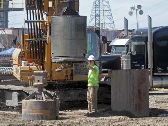 After holes are drilled for new bridge supports, workers fill them with a slurry mix to keep the inner walls from collapsing, as part of repairs to the I-495 bridge, Friday, June 20, 2014.